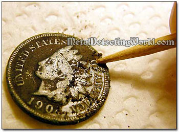 Cleaning Coin with a Toothpick