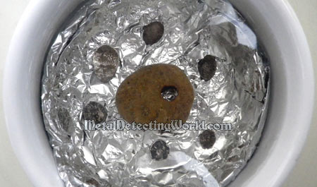 Tarnished Silver Coins Are Placed On Aluminum Foil Submerged In Electrolyte