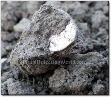Partially Visible Wire Coin Inside the Dirt Lump
